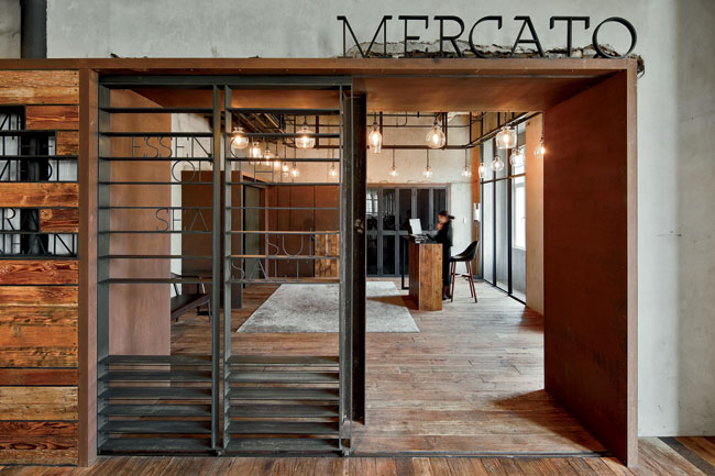 Evoking the historical context of the locale, the entrance features a Victorian plaster ceiling and reclaimed wood floor juxtaposed with a raw steel gate, graphic signage, and a suspended rail of glas
