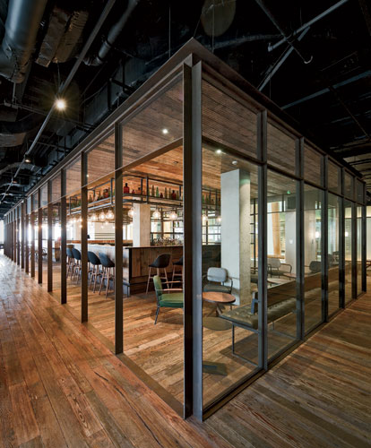The main space recalls a street market, with a cocktail bar and pizza bar at its center—both encased in steel mesh and wire glass boxes with recycled wood canopies. A network of tube steel membe