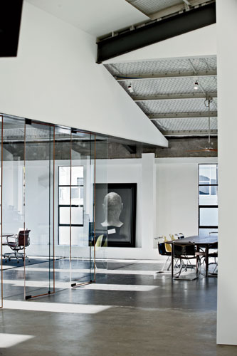 The exposed beams and rough concrete floors of the original structure remain intact, with the glass panels that divide the offices from the warehouse being Fearon Hay's only major insertion.