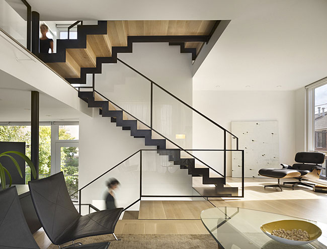 The interior of the Philadelphia townhouse spirals around a sparely designed open stair with patinated steel railings and bleached oak treads.