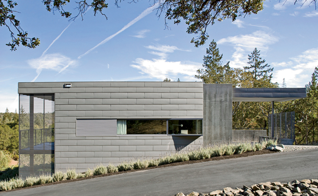 The architects chose a monochromatic palette, but experimented with texture. Zinc panels, concrete walls, and stained redwood screens unify the exterior.