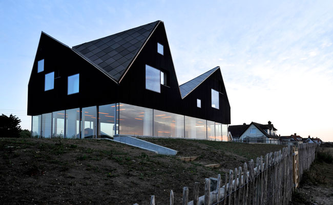 The jagged, timber-clad second story of the Dune House, on the east coast of England, contains bedrooms and bathrooms.