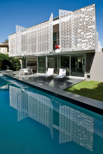 The perforated-metal screens on the third floor conceal balconies overlooking a basalt-edged lap pool.