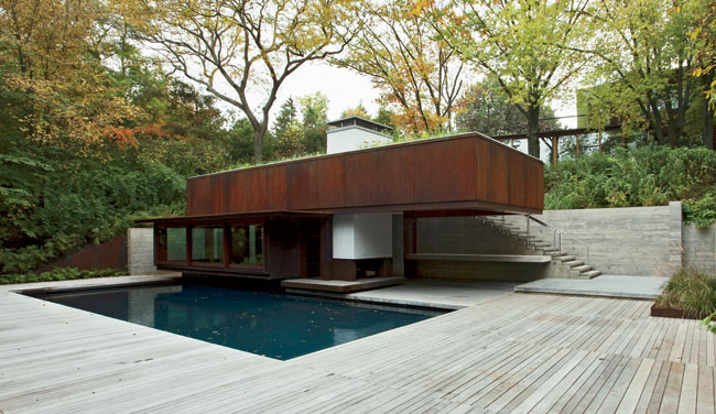 A board-formed-concrete retaining wall and stair lead to the pool house.