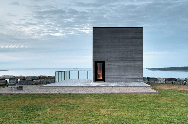 Visitors to the Cliff House approach an unfenestrated facade, punctuated by a single doorway.