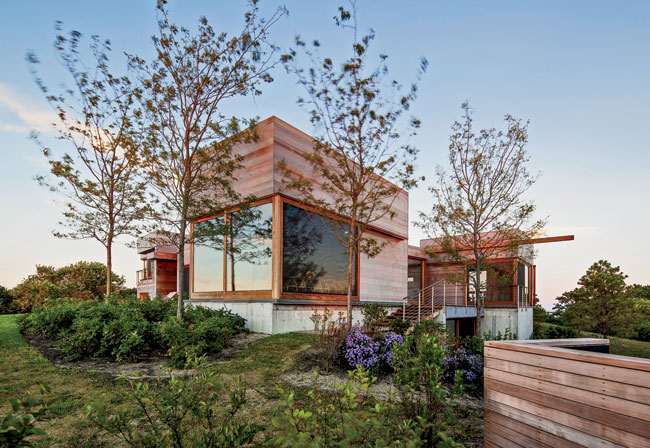 Nestled within a richly wooded site on a narrow strip of land, the 6,300-square-foot house comprises a series of cedar-clad boxes of varying heights with large, fully operable windows.
