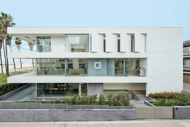 The minimalist three-story house is punctuated by movable walls on the top floor and deep overhangs.