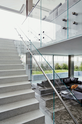 A central glass stair maintains an airy feeling in the living room.