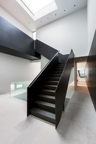 The sculptural stair that connects the two wings of the house is custom-fabricated from folded blackened-steel plate.
