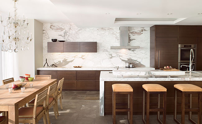 Montpelier limestone floors and Calacatta marble walls and counters define the crisp, open-plan kitchen.