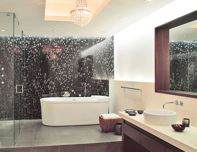 The master bath's soaking tub and glass-enclosed shower are backed by a slab of Black Spring granite.