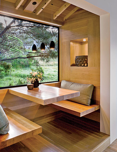 A cedar-clad breakfast nook overlooks the verdant property through expansive panes of glass.