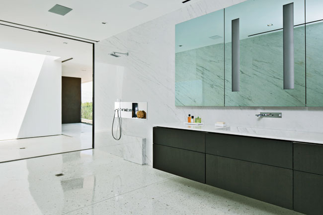 In the master-bathroom suite, his bath is one large shower room with drainage built into the terrazzo floor.