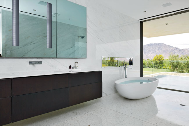 The marble-topped oak vanity spans 12 feet in length. Her bath features a freestanding egg-shaped tub with a rain shower just beside it. Glass pocket walls in both baths give way to outdoor terraces.