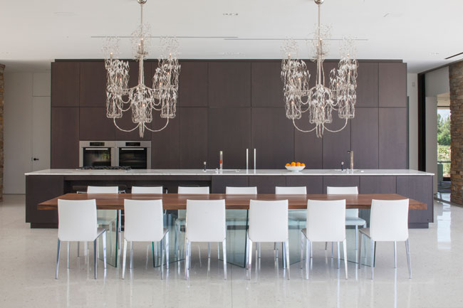 "The dining table appears to float, thanks to its base of angled glass fins. The architects installed two chandeliers because ""one is a focal point, but two create a line,"" says Kelly."