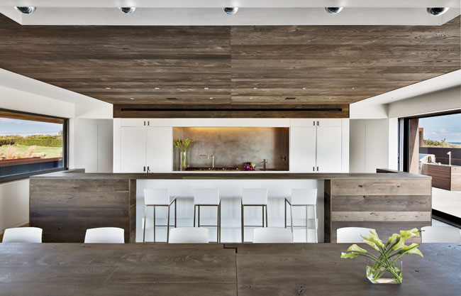 Oak dominates the kitchen, save for white lacquer cabinetry that conceals appliances and frames a stainless-steel backsplash.