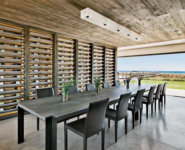 Flooring throughout is poured concrete. For the custom wine rack, the architects used mirror-glass to capture reflections of movement, while long swaths of mesh fabric hold the bottles. The custom cei