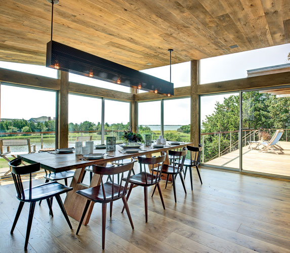 Located just to the right of the kitchen on the house's east side, the dining room opens to a series of decks and overlooks a backyard pond. The custom light fixture reintroduces the black perforated