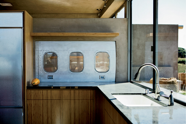A three window stretch of 747 fuselage forms a whimsical pass-through from the kitchen to the client's study.