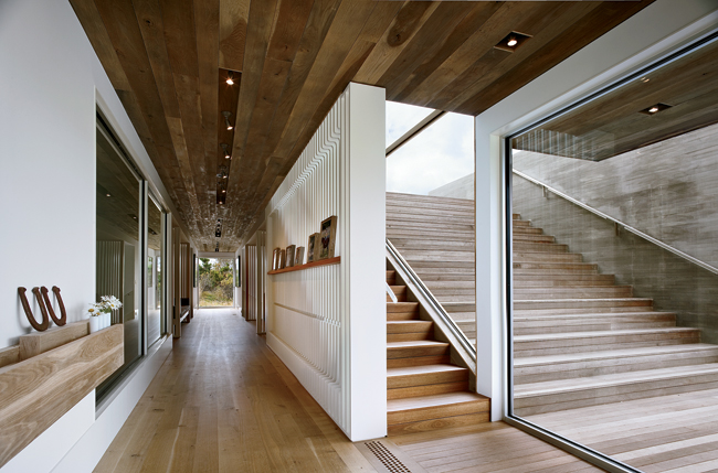 On the lower level, a sculptural wood screen functions as a gallery wall and guardrail.
