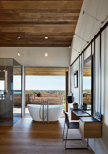 Sliding glass doors allow bathers to enjoy breezes and views in the master bath. The architects were inspired by horseshoes when designing the blackened stainless steel shelving, which also appears in