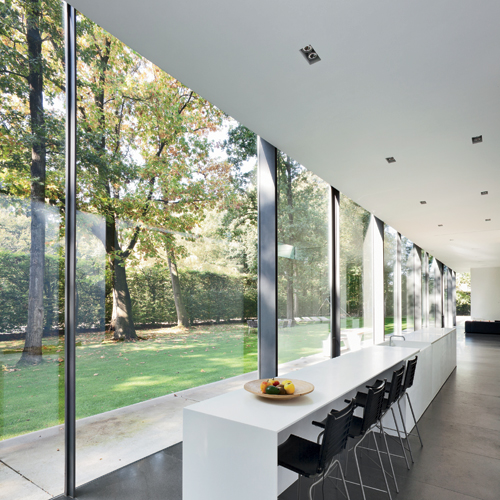 The elongated kitchen faces directly onto the tree-studded lawn.