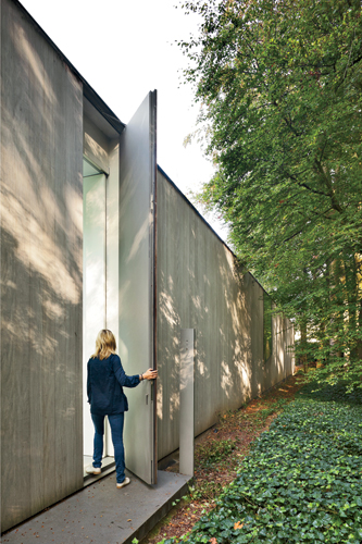 For the front door, Govaert cut out a panel in the back of the wood wall from which the glazed living spaces are extruded. The door opens onto a glazed bridge overlooking the driveway.