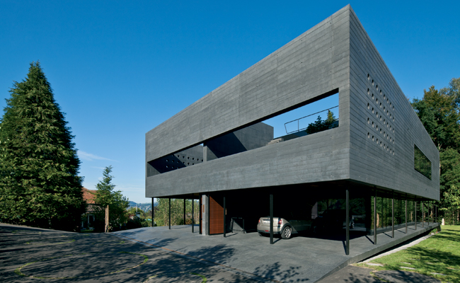The front door for both twin houses is entered through the carports contained within the concrete volume.