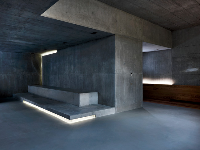 Cove lighting in the basement, a family and party space, adds drama to the board-formed concrete volumes.