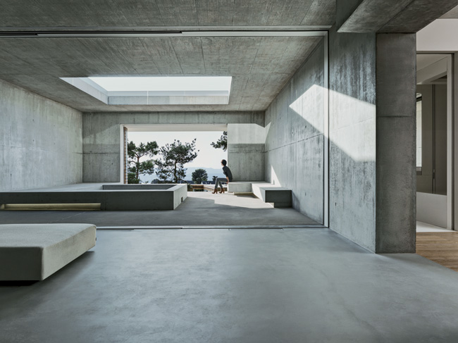 A cutout in the terrace brings daylight to an open-air room on the ground floor. This space connects to the main living area by a sliding glass wall and features concrete benches and a square void for