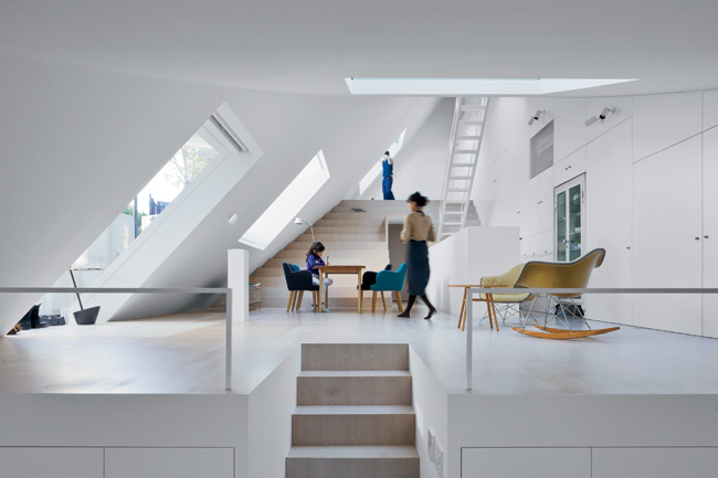 Inside, level changes and furnishings divide the space, enabling family members to remain in each other's presence even when engaged in different activities. Bleacherlike stairs lead up to a sleeping