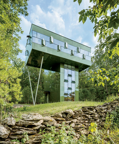 The entirely glass-clad structure comprises a four-story tower containing a stair, bedrooms, bathrooms, and a kitchen, and a primary living space cantilevered 30 feet off the ground.