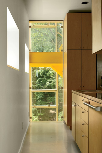 Although the kitchen is only about 175 square feet, it is open at each of its corners to the main living area or the stair, with its yellow risers and treads. Since the kitchen is part of the thermal