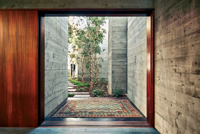The fine grain of Douglas fir formwork adds texture to concrete walls, which continue on the inside of the main entry from the outside.