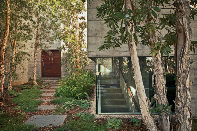 The house presents a mostly solid exterior to its neighbors. It opens up to the elements with an entry courtyard, interior gardens, and voids bringing air and light to areas such as the dining room on