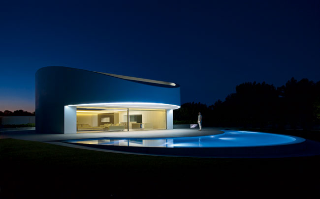 The 5,400-square-foot house reads as an elegant industrial object, especially when lit up at night. A curving swimming pool responds to the elliptical form of the house.