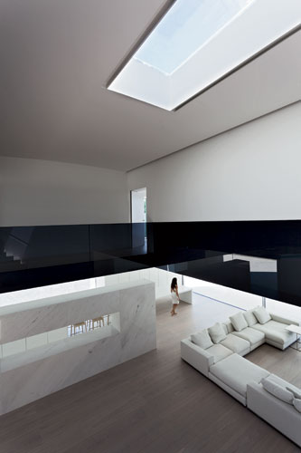 Dark smoked-glass balustrades on the second floor provide a visual counterpoint to the white interiors.