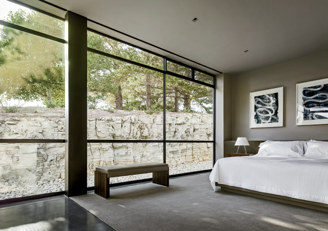 A guest bedroom looks out to a wall of Carmel stone.