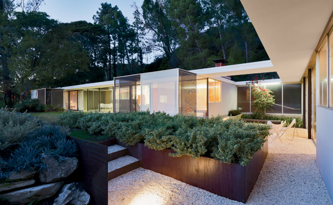 While corrugated steel sheathes the house's entry side, its private faces are enclosed in sliding-glass panels. The two screened-in patios were added sometime after the home's original con