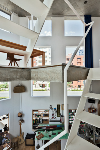 Consistent with the light-filled, airy interior, thin steel stairs connect the client's atelier and dining area, blending his studio and residence into one fluid, vertically stacked space. Compe