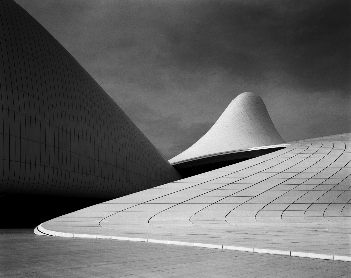 <br><h9>Heydar Aliyev Centre by Zaha Hadid Architects <br>Baku, Azerbaijian, photo © Hélène Binet, courtesy Ammann Gallery, 2013</h9><p>   </p><h6><strong>HÉLÈNE BINET</strong><br> Photographer based in London<p>   </p>I have been working for 30 years to capture architectural space in photographs. I spend about half my time in the commercial world and half my time doing personal work. Recently I've been photographing traditional Korean architecture, which is astonishing. The photos may become a book.<p>   </p> There are a few architects I've been working with for many years, including Peter Zumthor and Caruso St John. I like to have long relationships—I feel I grow with the architects; it's not just shooting and going home. Zaha Hadid was very important to my career. I shot all of her buildings starting with Vitra. There was something primordial about her work, something very deep, which I hope I brought out in my photos. She's often been misunderstood. Some people see her work as fashionable; I was never interested in that.<p>   </p> I shoot mostly in black-and-white. The way we experience space is a complex thing, and color can compete with that experience. I go in the other direction. I prefer silence. I shoot on film; I don't touch digital. I use a 4x5 camera called an Arca-Swiss—you put a film plate in and put a blanket over your head. It's expensive, and it's slow. Each image is a commitment. It's like a performance: you have to be very good in the moment; you don't get a chance to fix it later. I might make 20 images in a day, eight or nine that I'm happy with. I do all the printing myself, choosing everything: the paper, the contrast. The actual print is very important to me. A reproduction of the work is not the work.